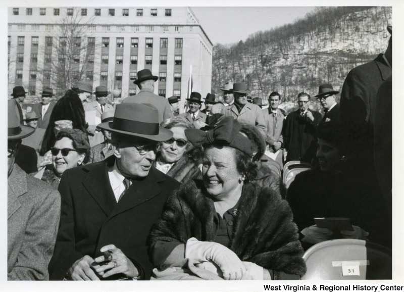 A photograph of a unidentified couple sitting during Governor Cecil Underwood's inauguration. In the background, various unidentified people are sitting and standing.
