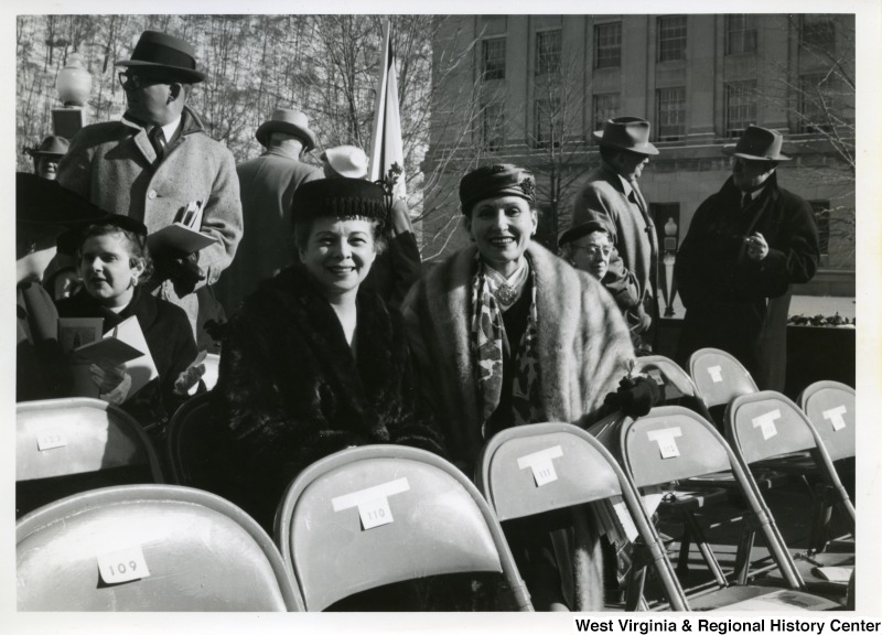 A photograph of two unidentified women sitting in seats 124 and 125 at Governor Cecil H. Underwood's inauguration.