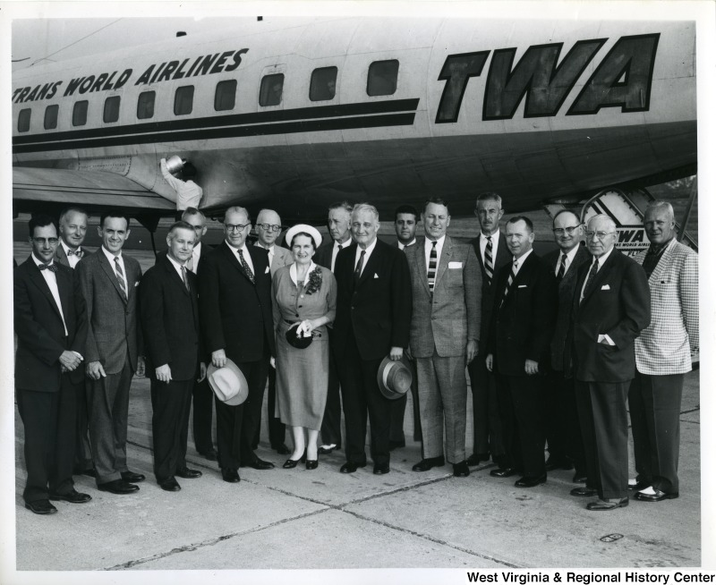 A group of unidentified people standing in front of a Trans World Airlines (TWA) plane with Congressman Arch Moore, who is the fourth person from the left.