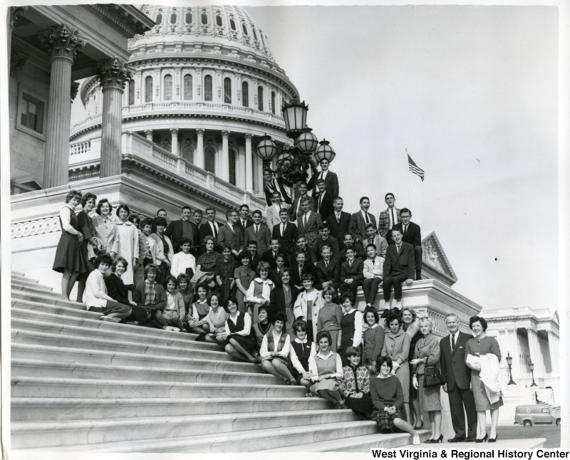 A group of unidentified individuals posing on the Capitol steps with Congressman Arch Moore, Jr. and his wife Shelley Riley Moore.