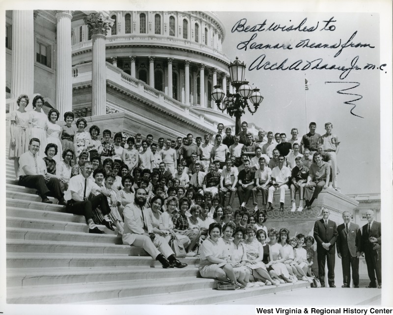"Congressman Arch Moore, Jr. and a group of unidentified people sitting on the steps of the Capitol building. The photograph is signed, ""Best wishes to Leanore Means from Arch A. Moore, Jr.  m.c."""