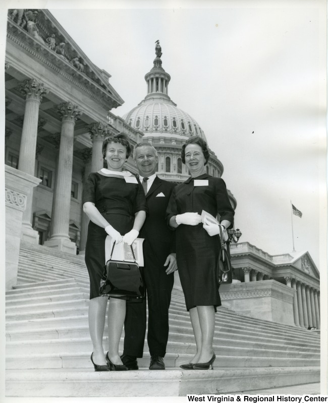 Congressman Arch Moore, Jr. and two unidentified women standing on the steps of the Capitol Building.