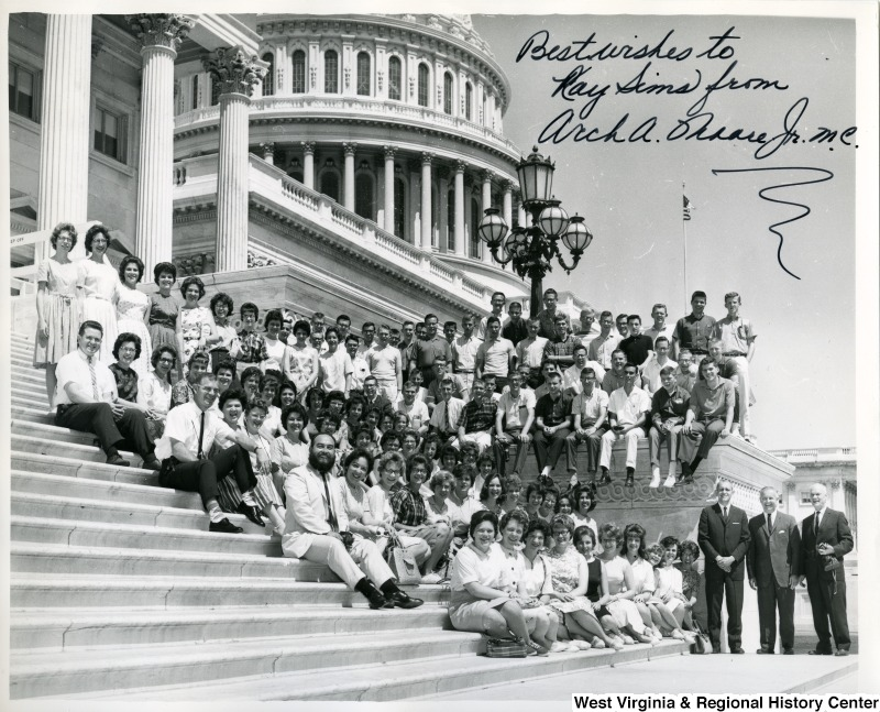 "Congressman Arch Moore, Jr. with a large unidentified group of people sitting on the Capitol building steps. The photograph is signed ""Best wishes to Ray Sims from Arch A. Moore, Jr."""