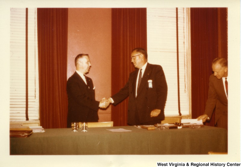Congressman Arch Moore, Jr. shaking hands with an unidentified man. Another unidentified man is on the edge of the photograph (R side) laying a piece of paper on the table.
