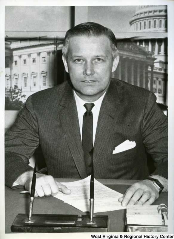 Congressman Arch Moore, Jr. is sitting behind his desk. He is looking at the camera and a letter is laying in front of him.