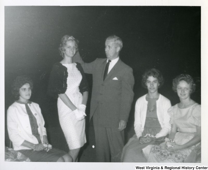 Congressman Arch Moore, Jr. (center) standing next to an unidentified woman wearing a tiara. Two unidentified women are sitting on the right and one on the left.