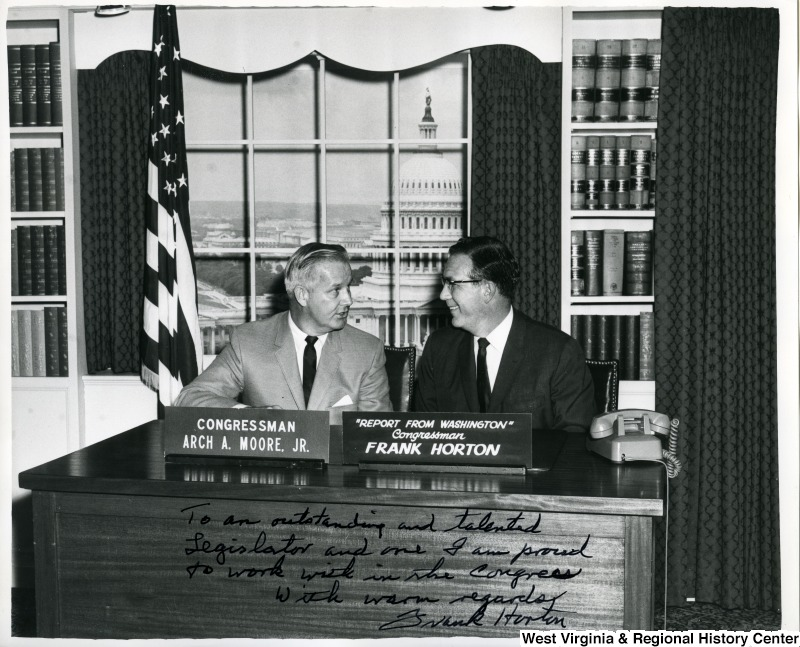 "Congressmen Arch A. Moore, Jr. and Frank Horton (N.Y.) sitting at a desk talking. The photograph is signed, ""To an outstanding and talented legislator and one I am proud to work with in the Congress. With warm regards, Frank Horton""."