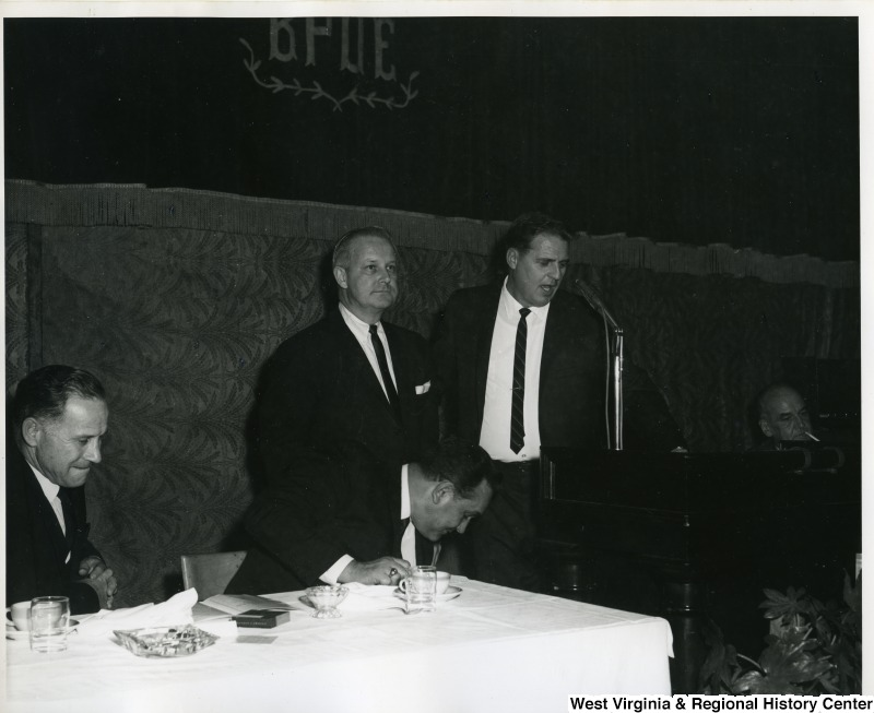 Congressman Arch Moore, Jr. standing next to an unidentified man who is speaking at the Silver Anniversary Banquet of Iron Workers Local Union No. 549. The Silver Banquet was held at the Elks Lodge in Wheeling, W.V.
