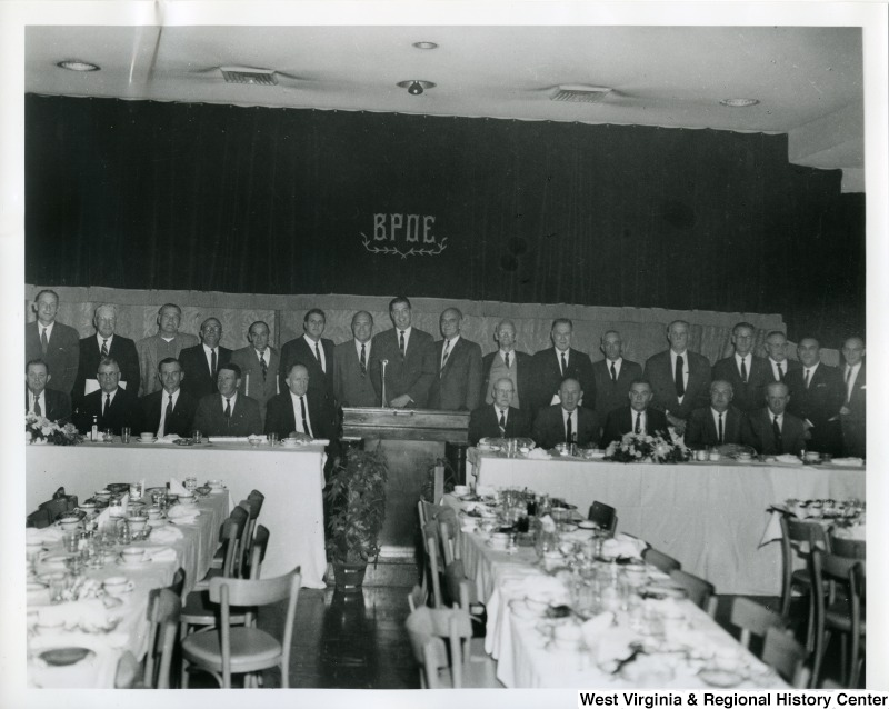 "The members present at the Silver Anniversary Banquet of the Iron Workers Local Union No. 549. The banquet was held at the Elks Lodge in Wheeling, W.V. Standing left to right: Fred Witzgall, Fred Adams, Emylin Rogers, Louis Goormastic, Joseph Richter, Wayne Mahurin, James R. Downes (General Secretary), John H. Lyons (General President), Wayne T. Brooks (Director of Industrial Relations Wheeling Steel Co.), Casper Schrimpf, Thomas Davis, Charles Gormastic, E.A. Barcus, John Cox, Ray E. Armstrong (General Organizer), Michael Barcheck (President of Iron Workers Local Union No. 549), and Richard Steele (Financial Secretary-Treasurer of Iron Workers Local Union No. 549).  Seated left to right: John Ellis, Jack Montgomery, Louis Tomich, Sr., Ellis Vickers, William Suddith, A.H. ""Dick"" Ingram, Joseph Dzwonkowski, Robert Bosley, Marshall McCorkle, and French Underwood."