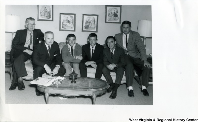 "Congressman Arch A. Moore, Jr. sitting on a couch with Robert K. ""Bob"" Holliday and four other unidentified men."
