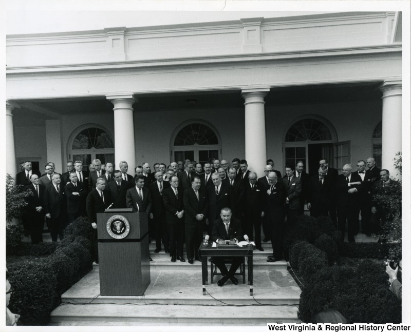 President Lyndon B. Johnson signing S. 3, the Appalachian Regional Development Act. The President is surrounded by members of Congress.