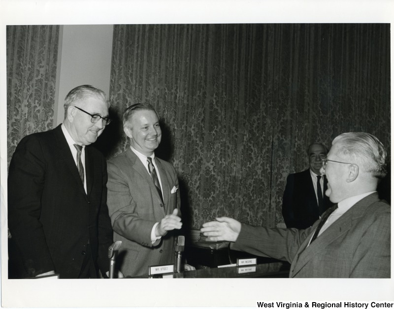 "Congressman Arch A. Moore, Jr. shaking the hand of a unidentified man. Congressman Thomas ""Tom"" Steed is standing beside Moore."