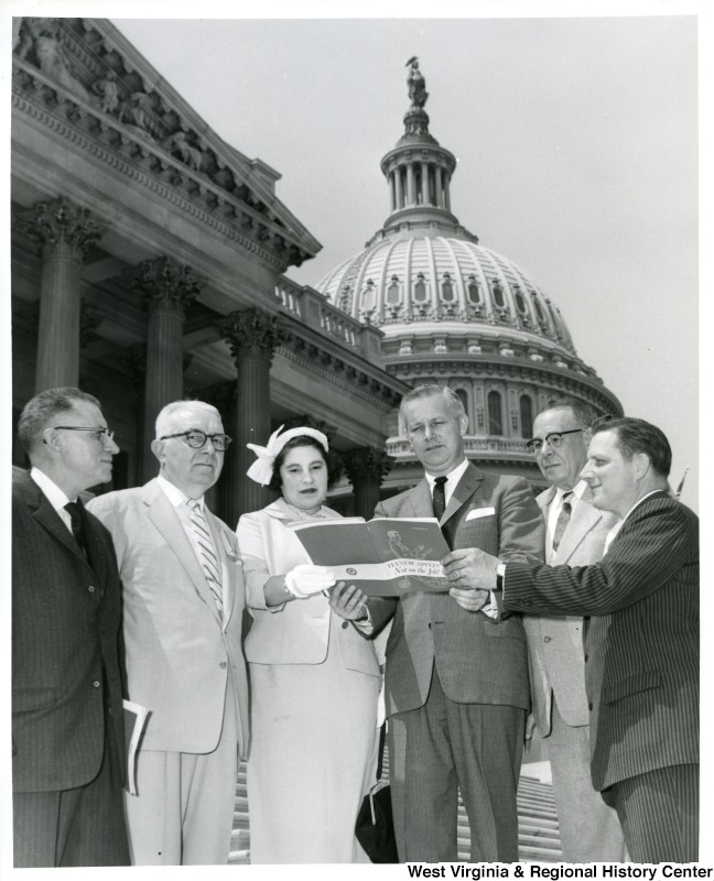 "Congressman Arch A. Moore, Jr. standing on the capitol steps with five unidentified people. He is holding the book ""Handicapped: Not on the Job!"""