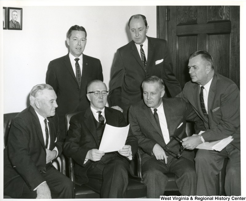 Congressman Arch A. Moore, Jr (front, second on the right) looking at a document being held by Congressman William M. McCulloch. Four other unidentified congressmen are reviewing the document as well.