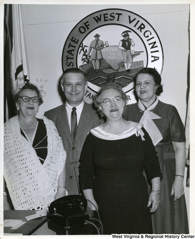 Congressman Arch A. Moore, Jr. standing with three unidentified women. The West Virginia Seal is in the background.