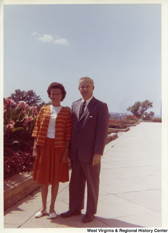 A colored photograph of Congressman Arch A. Moore, Jr. standing with an unidentified woman.  Flowers can be seen beside and behind them.
