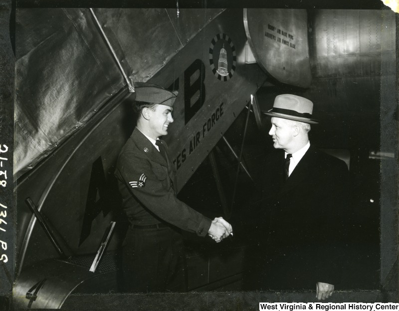 Airman Marion L. Mussili shaking hands with Congressman Arch A. Moore, Jr.  immediately after their arrival at MATS (Military Air Transport Service) terminal, Andrews AFB (Air Force Base), Maryland from Europe. Congressman Moore interceded in the confinement of Airman Mussili by the Greek Government after his conviction for hitting a pedestrian with a military vehicle. Moore then brought the airman back to the states with him.