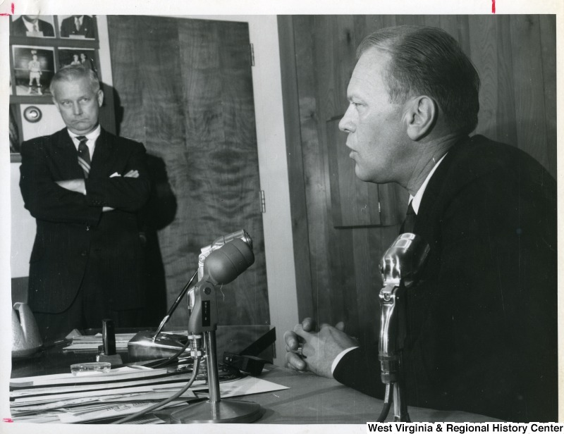 Congressman Arch A. Moore, Jr. standing to the side watching Gerald Ford talk into some microphones.