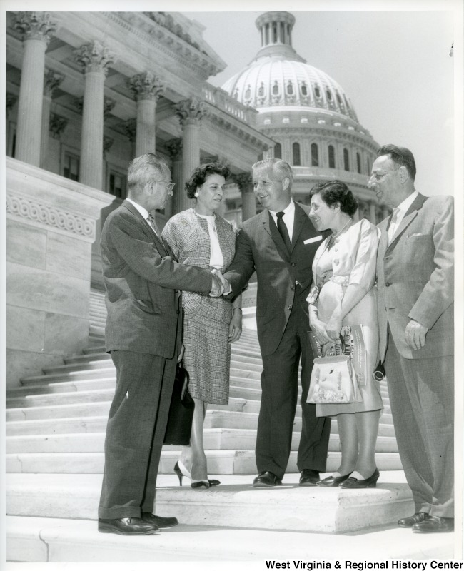 Congressman Arch A. Moore, Jr. shaking hands with an unidentified man on the steps of the Capitol Building. Two unidentified women and a man are standing with him.
