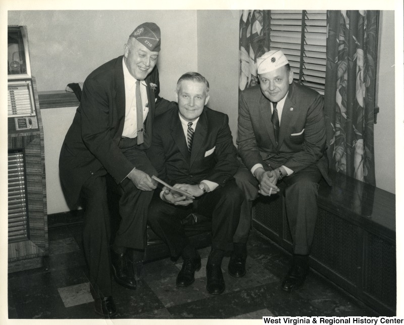 Congressman Arch A. Moore, Jr. sitting with two unidentified veterans.