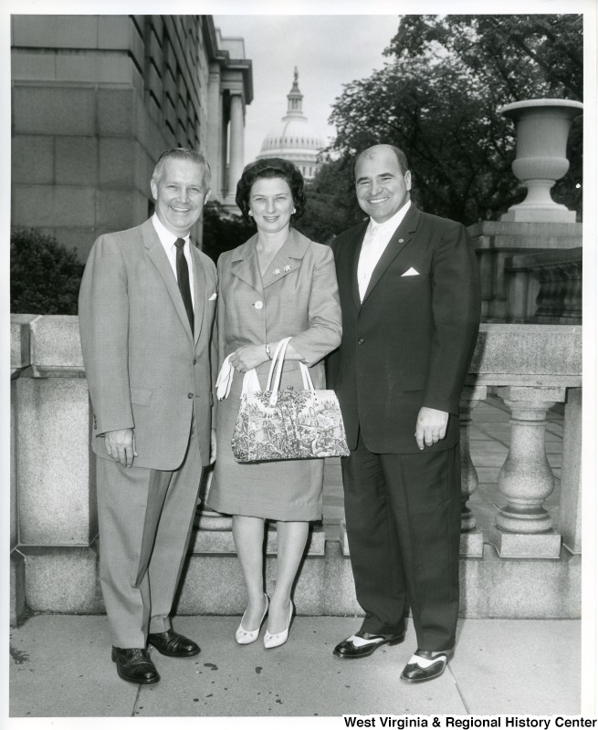Congressman Arch A. Moore, Jr. (left) standing with his wife, Shelley Moore, and an unidentified man. The Capitol Building can be seen in the background.