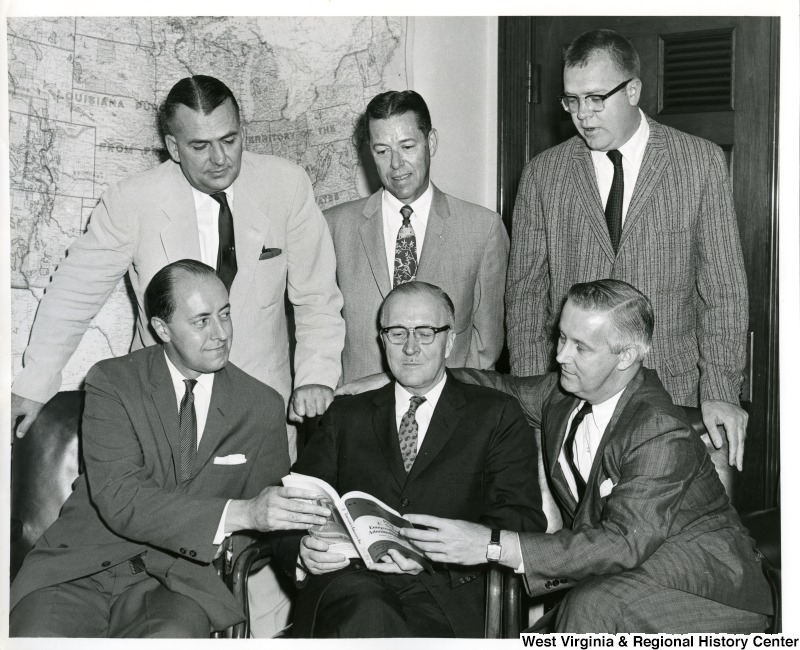 Congressman Arch A. Moore, Jr. (seated, right), Congressman William M. McCulloch (center), and four others looking at the book Congressional and Administrative News.