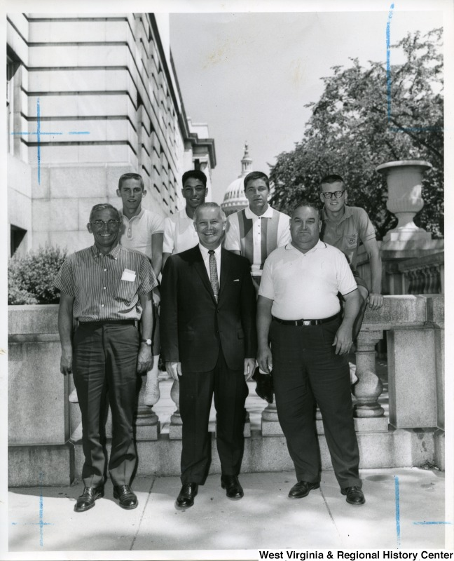Congressman Arch A. Moore, Jr. (center) surrounded by an unidentified group of men. The Capitol Building can be seen in the background.