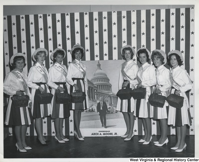 Eight unidentified women wearing Re-Elect Congressman Arch A. Moore, Jr. sashes and holding baskets. In the center is a poster of Moore walking away from the Capitol.