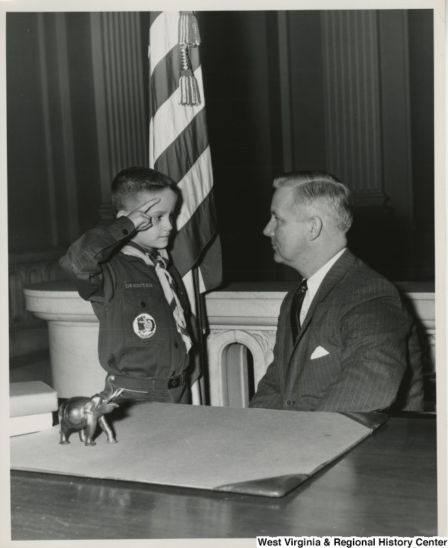 Congressman Arch A. Moore, Jr. getting saluted by an unidentified Cub Scout.