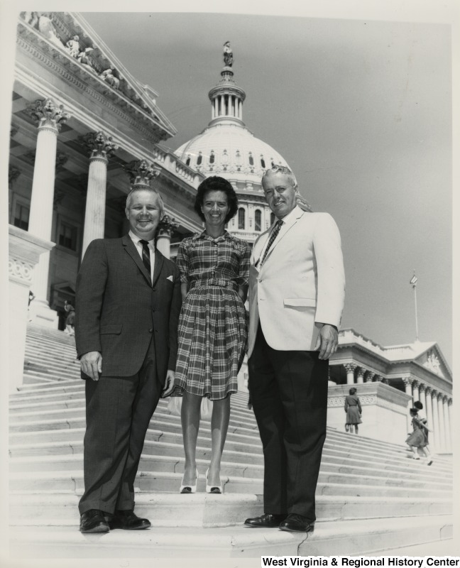 Congressman Arch A. Moore, Jr. standing with an unidentified woman and man on the steps of the Capitol.