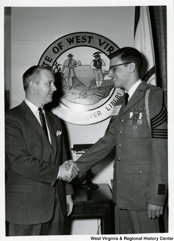 "Congressman Arch A. Moore, Jr. shaking hands with an unidentified  man. The man has a pin on his chest stating ""I speak for democracy."""