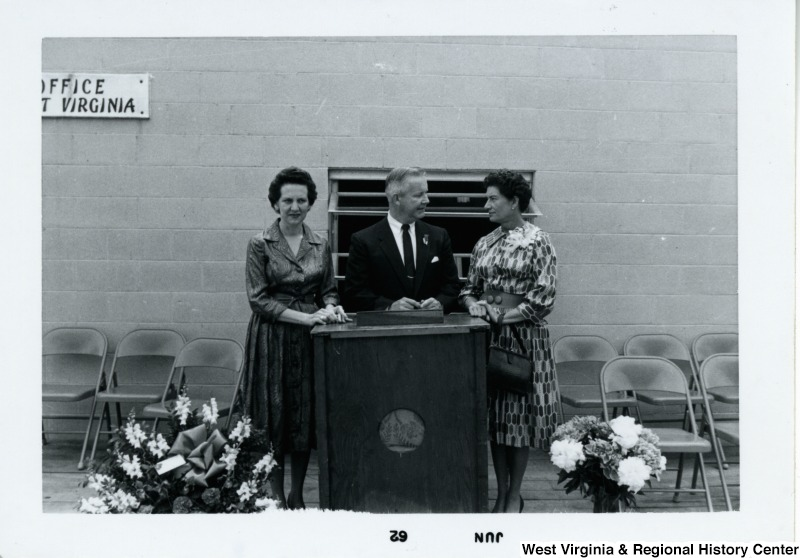 Congressman Arch A. Moore, Jr. standing at a podium with two unidentified women.