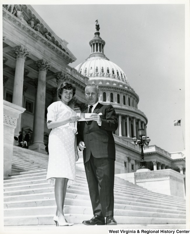 Congressman Arch A. Moore, Jr. standing with an unidentified woman on the steps of the Capitol. They are holding a piece of paper.