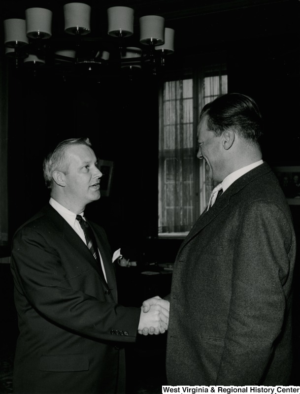Congressman Arch A. Moore, Jr. shaking hands with an unidentified man