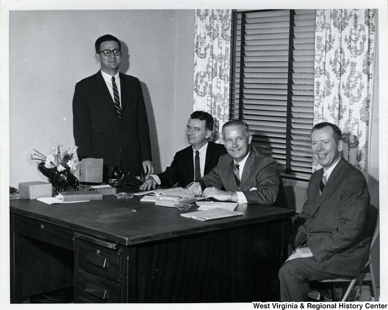 Congressman Arch A. Moore, Jr. seated at a desk with two unidentified men. Another unidentified man is standing on the far side (left) against the wall.