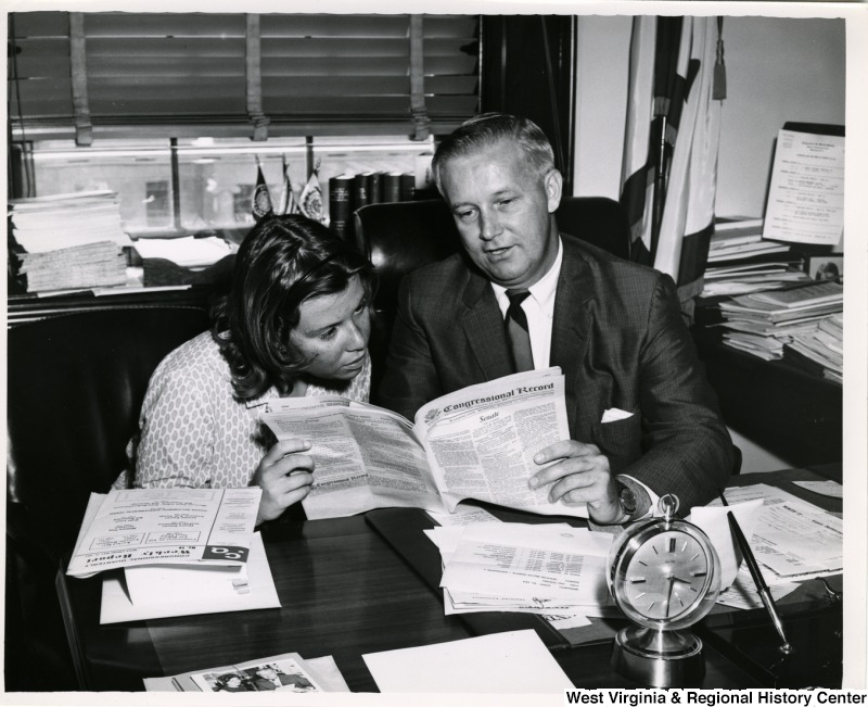 Congressman Arch A. Moore, Jr. showing a girl the Congressional Record for Monday, August 12, 1963.