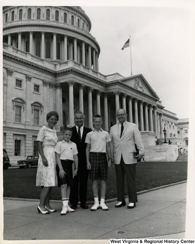 Congressman Arch A. Moore, Jr. standing with an unidentified family of four in front of the Capitol Building.