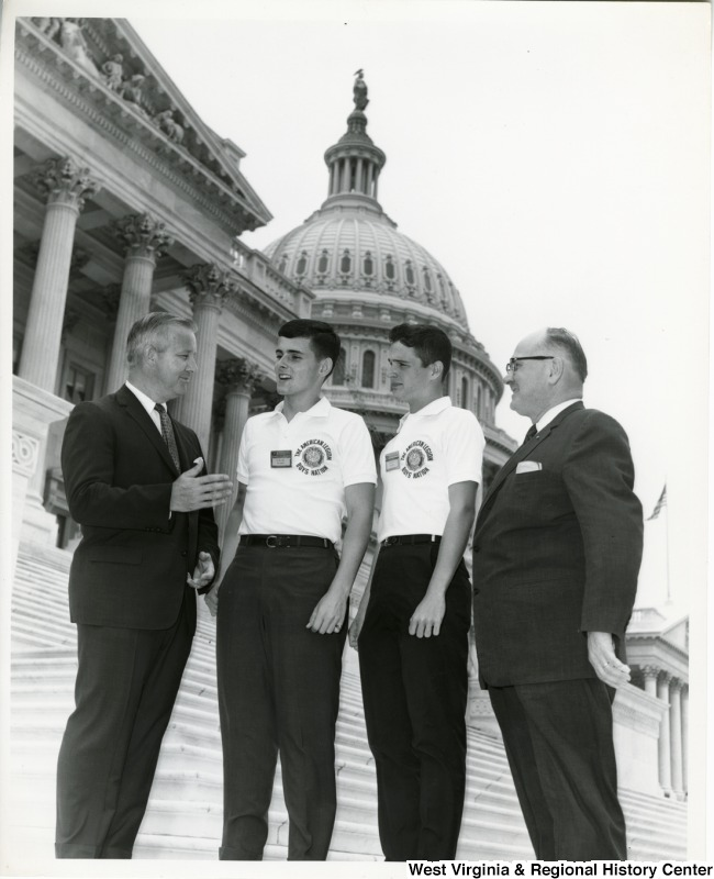 Congressman Arch A. Moore, Jr. having a conversation with two young men from the American Legion Boys Nation on the steps of the Capitol Building. An unidentified man is also standing with them.