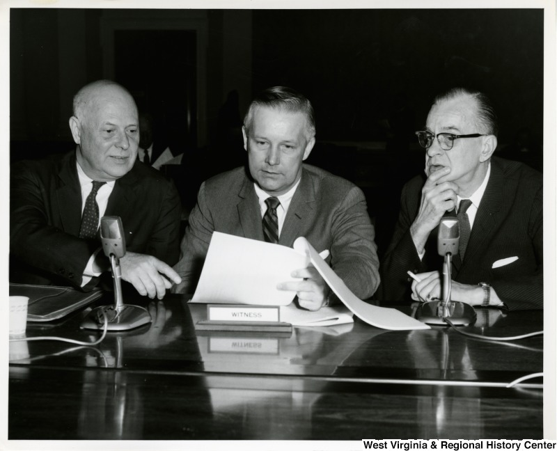 Congressman Arch A. Moore, Jr. discussing a document with two others. A witness plaque is in front of Moore.
