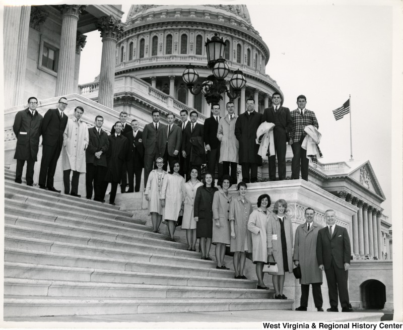 Congressman Arch A. Moore, Jr. standing on the steps of the Capitol with an unidentified group of men and women.