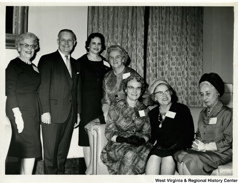 Congressman Arch A. Moore at a reception of the National Federation of Business and Professional Women's Club, Inc. in honor of members of the 88th Congress. The reception was at the Mayflower Hotel in Washington, D.C. Left to right: Mrs. Mabel Grimes, First Vice President of Morgantown; Congressman Arch A. Moore, Jr.; Miss Pearl Jett, State President of West Union; Dr. Corma Mowery, NEA  Director; Mrs. Loraine Smith, State Corresponding Secretary of West Union; Mrs. Kathryn Guth, First Vice President of Washington, D.C. Federation and native of Grafton; and Mrs. Lillian Majolly, Director of National Foundation of Washington, D.C., and native of Morgantown.