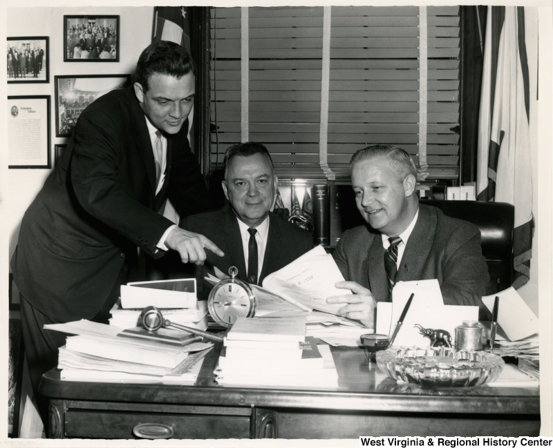 Congressman Arch A. Moore, Jr showing the bill H.R. 7152, the Civil Rights Act of 1964, to two unidentified men.