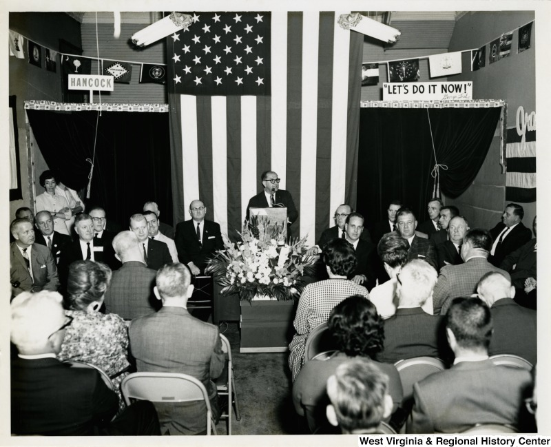 An unidentified man is giving a speech at a re-elect Moore campaign event. Congressman Arch A. Moore, Jr. is seated on the first seat on the left side in the front row facing the audience.