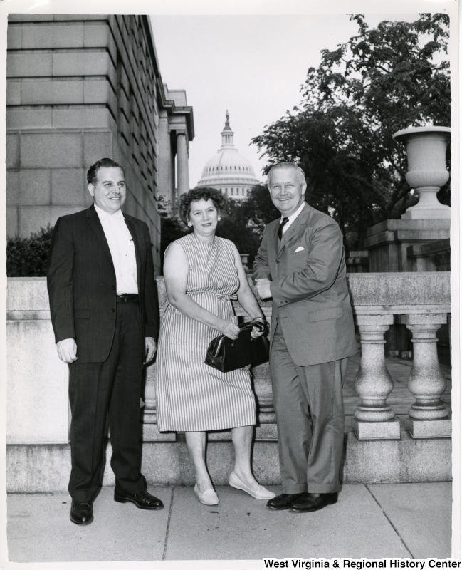 Congressman Arch A. Moore, Jr. standing with a unidentified man and woman. The Capitol Building can be seen in the background.