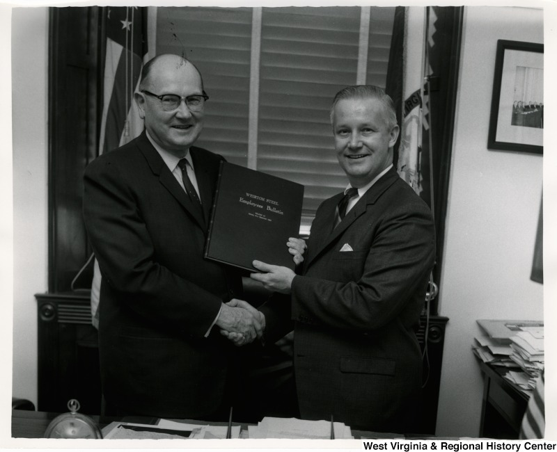 Congressman Arch A. Moore, Jr. and an unidentified man holding the Weirton Steel Employees Bulletin Volume 30, January through December 1963. The two men are also shaking hands.