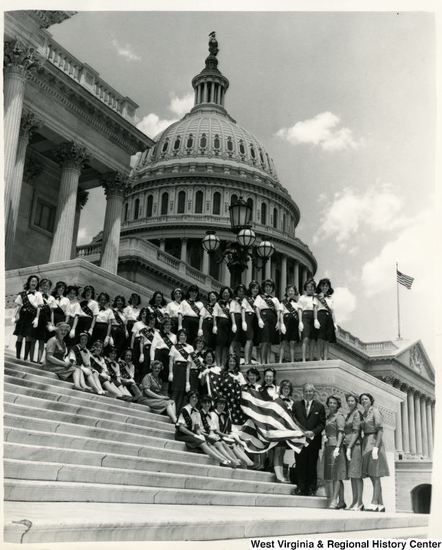 Congressman Arch A. Moore, Jr. standing on the steps of the Capitol with a group of Girl Scouts from Troops 260, and 241.  Some of the girls are holding a American Flag.