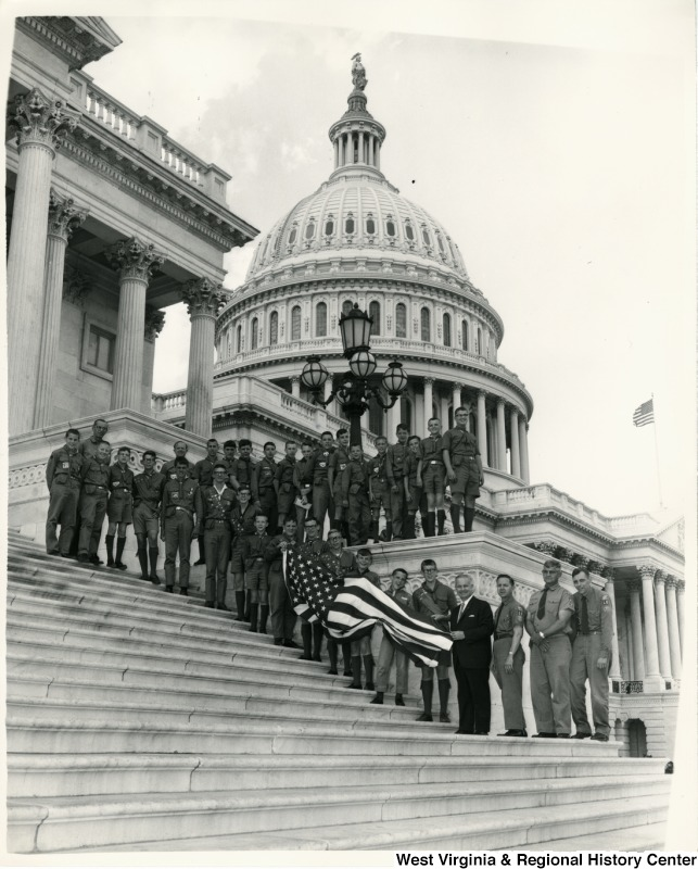 Congressman Arch A. Moore, Jr. standing on the steps of the Capitol with a group of Boy Scouts from Troop 10. Some of the Boys Scouts are holding a American Flag.