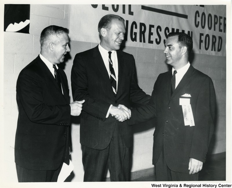 Congressman Gerald Ford shaking the hand of a delegate and candidate. Congressman Arch A. Moore, Jr. is standing beside Ford.