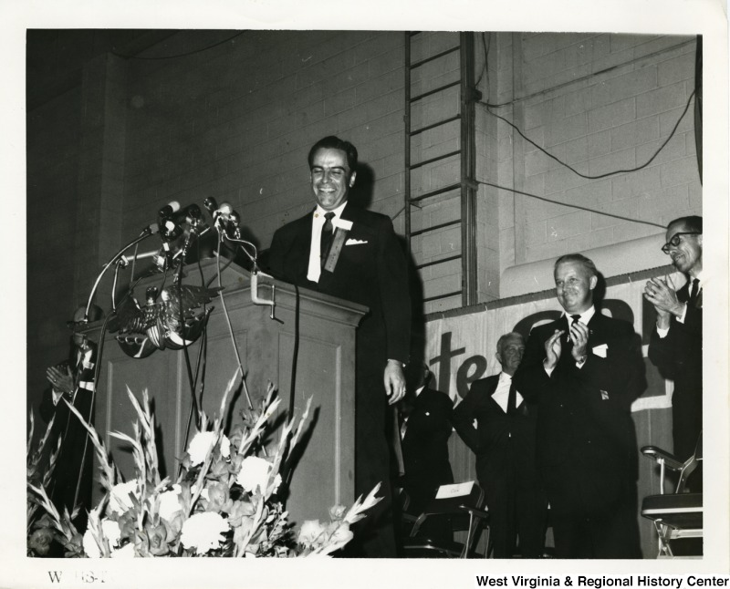 Governor Cecil H. Underwood at a podium speaking at a Goldwater/Miller campaign rally. Congressman Arch A. Moore, Jr. is standing behind him, with other unidentified men,  clapping.