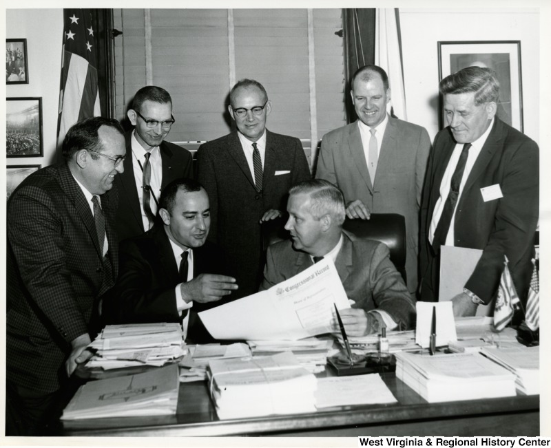 Congressman Arch A. Moore, Jr. showing members of the United Federation of Postal Workers the Congressional Record. The postal clerks visited Washington to confer with congressional leaders and government officials on postal pay. Left to right: Henry C. Hoffman (Fairmont), Carlo A. Martina (Clarksburg), Melvin L. Osborne (Clarksburg), Mr. Robert Hawkins (Fairmont), Homer Glaspell (Clarksburg), and Mr. Clyde W. Hagedorn (Morgantown).